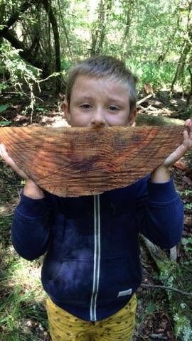 Un enfant en colonie de vacances place un morceau de bois en forme de sourire devant sa bouche