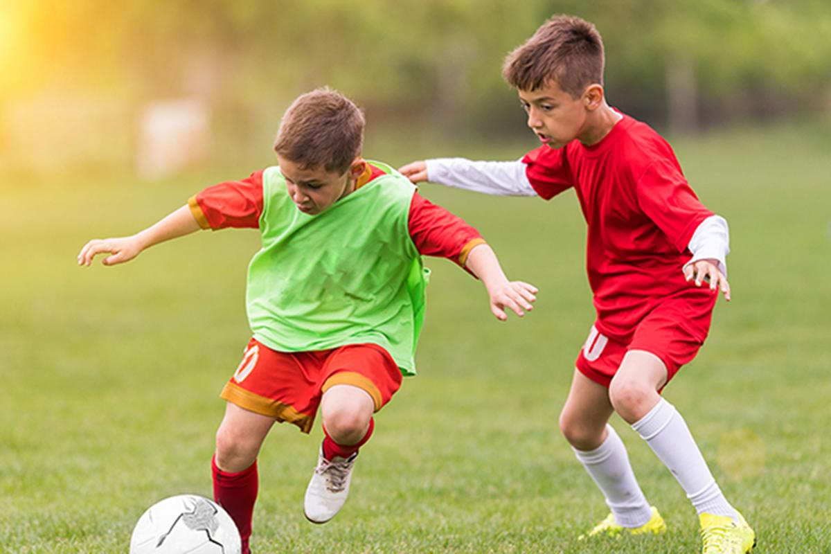 deux enfants jouant au football en colonie de vacances