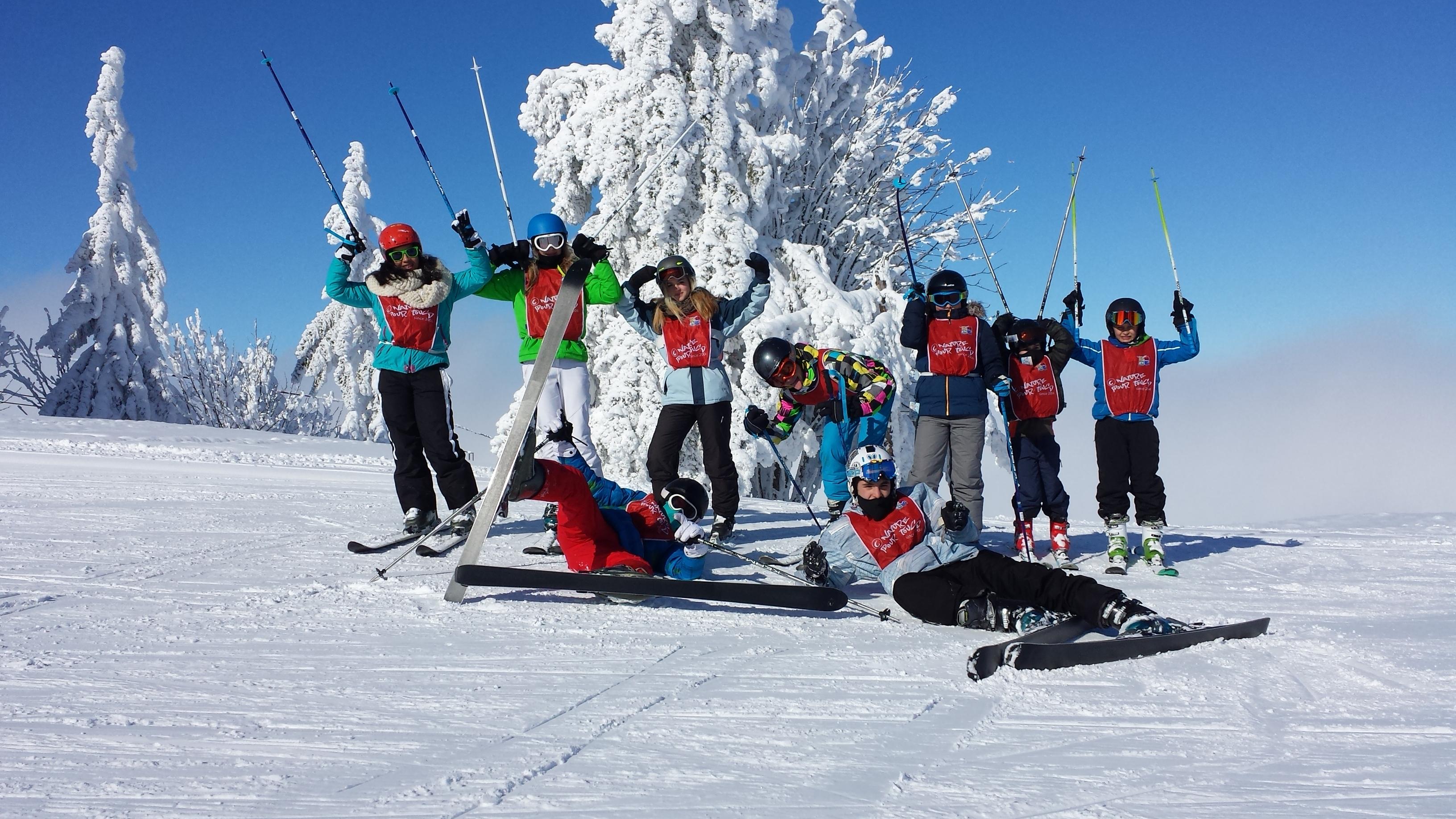 9 jeunes skieurs en ski, bâtons en l'air devant un arbre totalement enneigé sur une piste de ski en colonie de vacances supernova Juniors